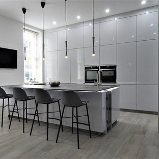 Design ideas for a mid-sized modern l-shaped open plan kitchen in Kent with an undermount sink, flat-panel cabinets, white cabinets, black appliances, with island and blue benchtop.