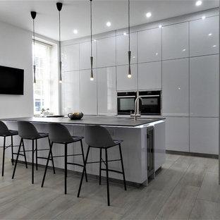 Свежая идея для дизайна: угловая кухня-гостиная среднего размера в стиле модернизм с врезной раковиной, плоскими фасадами, белыми фасадами, черной техникой, островом и синей столешницей - отличное фото интерьера