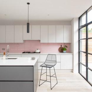 Mittelgroße Moderne Küche mit flächenbündigen Schrankfronten, Quarzit-Arbeitsplatte, Küchenrückwand in Rosa, Glasrückwand, hellem Holzboden, Kücheninsel, weißer Arbeitsplatte, Waschbecken, weißen Schränken und beigem Boden in London