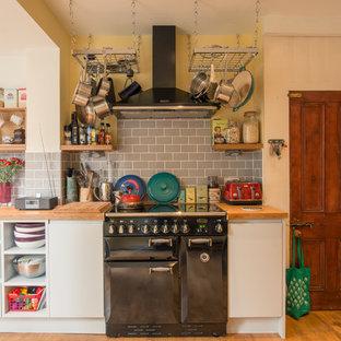他の地域の中サイズのエクレクティックスタイルのおしゃれなキッチン (エプロンフロントシンク、フラットパネル扉のキャビネット、グレーのキャビネット、木材カウンター、グレーのキッチンパネル、サブウェイタイルのキッチンパネル、白い調理設備、無垢フローリング、アイランドなし) の写真