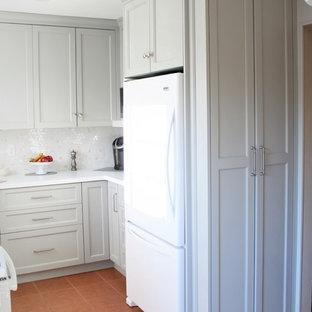 Inredning av ett klassiskt litet vit vitt kök, med en undermonterad diskho, skåp i shakerstil, grå skåp, bänkskiva i kvarts, vitt stänkskydd, vita vitvaror, terrazzogolv, rött golv och stänkskydd i mosaik
