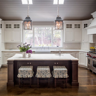 Farmhouse u-shaped dark wood floor enclosed kitchen photo in San Francisco with a farmhouse sink, beaded inset cabinets, white cabinets, white backsplash, an island and paneled appliances