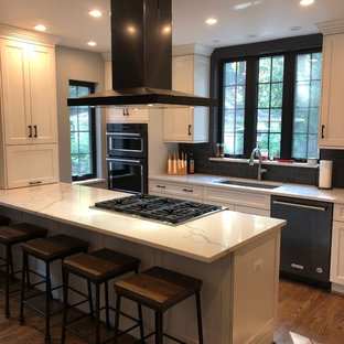 Mid-sized transitional u-shaped eat-in kitchen in Detroit with an undermount sink, recessed-panel cabinets, white cabinets, recycled glass benchtops, black splashback, ceramic splashback, stainless steel appliances, medium hardwood floors, brown floor and white benchtop.