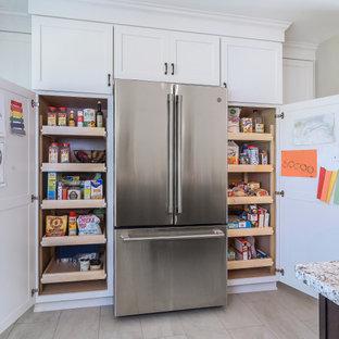 フィラデルフィアの中くらいのエクレクティックスタイルのおしゃれなキッチン (エプロンフロントシンク、シェーカースタイル扉のキャビネット、白いキャビネット、御影石カウンター、グレーのキッチンパネル、磁器タイルのキッチンパネル、シルバーの調理設備、磁器タイルの床、ベージュの床、マルチカラーのキッチンカウンター) の写真