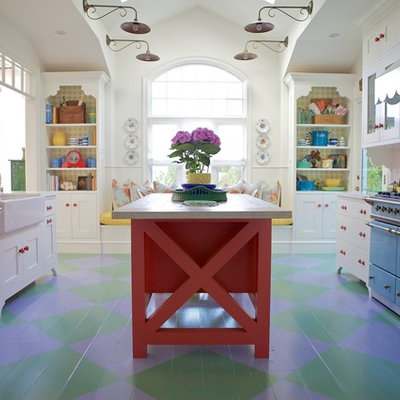 Example of a beach style painted wood floor and multicolored floor kitchen design in Los Angeles with a farmhouse sink, white cabinets, quartz countertops, ceramic backsplash, an island and colored appliances