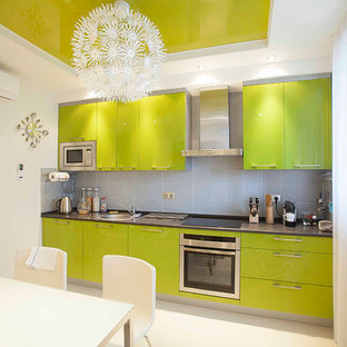 Contemporary l-shaped kitchen/diner in Moscow with a built-in sink, green cabinets, grey splashback and stainless steel appliances.