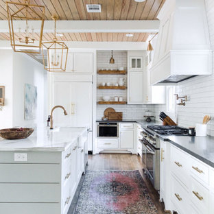 Farmhouse kitchen pictures - Example of a cottage l-shaped medium tone wood floor and brown floor kitchen design in Houston with a farmhouse sink, shaker cabinets, white cabinets, white backsplash, subway tile backsplash, an island and gray countertops