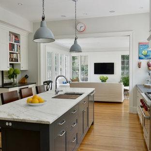 Foto på ett stort lantligt l-kök, med en undermonterad diskho, svarta skåp, rostfria vitvaror, mellanmörkt trägolv, en köksö, orange golv, skåp i shakerstil och marmorbänkskiva