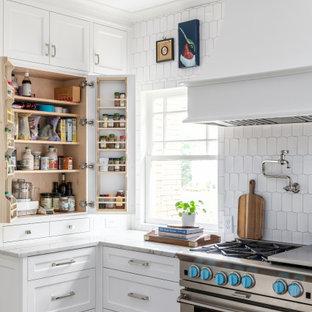 アトランタの広いビーチスタイルのおしゃれなキッチン (アンダーカウンターシンク、シェーカースタイル扉のキャビネット、白いキャビネット、珪岩カウンター、白いキッチンパネル、大理石のキッチンパネル、パネルと同色の調理設備、濃色無垢フローリング、茶色い床、白いキッチンカウンター) の写真