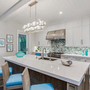 Esempio di una cucina tropicale con lavello sottopiano, ante in stile shaker, ante bianche, paraspruzzi multicolore, elettrodomestici da incasso, parquet scuro, un'isola e top bianco