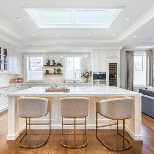 Bild på ett vintage grå grått l-kök, med en undermonterad diskho, luckor med infälld panel, vita skåp, marmorbänkskiva, grått stänkskydd, rostfria vitvaror, mellanmörkt trägolv och en köksö