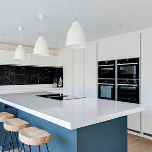 Inspiration for an expansive contemporary u-shaped kitchen/diner in Hertfordshire with an integrated sink, flat-panel cabinets, white cabinets, quartz worktops, black splashback, metal splashback, black appliances, painted wood flooring, an island, white floors and white worktops.