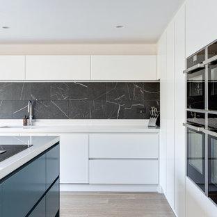 Geräumige Moderne Wohnküche in U-Form mit integriertem Waschbecken, flächenbündigen Schrankfronten, weißen Schränken, Quarzit-Arbeitsplatte, Küchenrückwand in Schwarz, Rückwand aus Metallfliesen, schwarzen Elektrogeräten, gebeiztem Holzboden, Kücheninsel, weißem Boden und weißer Arbeitsplatte in Hertfordshire