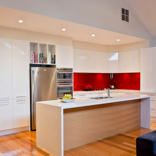Contemporary l-shaped kitchen in Melbourne with a double-bowl sink, flat-panel cabinets, white cabinets, red splashback, glass sheet splashback, stainless steel appliances, medium hardwood floors, with island, brown floor and white benchtop.