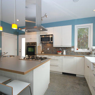 Mid-sized contemporary eat-in kitchen ideas - Eat-in kitchen - mid-sized contemporary u-shaped concrete floor eat-in kitchen idea in Minneapolis with a farmhouse sink, shaker cabinets, white cabinets, stainless steel appliances, laminate countertops, multicolored backsplash and glass tile backsplash