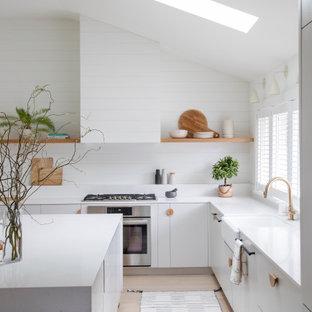 広いモダンスタイルのおしゃれなキッチン (エプロンフロントシンク、フラットパネル扉のキャビネット、グレーのキャビネット、珪岩カウンター、白いキッチンパネル、塗装板のキッチンパネル、パネルと同色の調理設備、淡色無垢フローリング、白いキッチンカウンター、三角天井) の写真