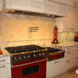 Bright red Viking range topped by a massive carved custom hood
