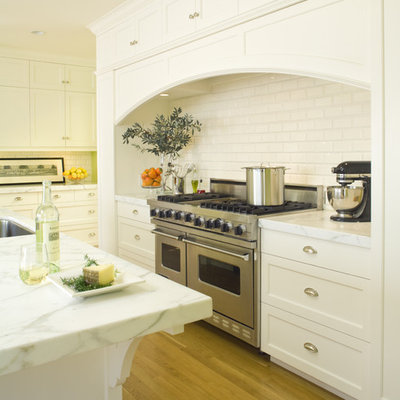 Example of a mid-sized classic l-shaped medium tone wood floor eat-in kitchen design in San Francisco with stainless steel appliances, subway tile backsplash, an undermount sink, recessed-panel cabinets, white cabinets, marble countertops, white backsplash and an island