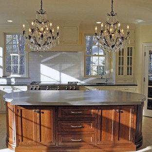 他の地域の中サイズのヴィクトリアン調のおしゃれなキッチン (エプロンフロントシンク、白いキャビネット、白いキッチンパネル、シルバーの調理設備の、シェーカースタイル扉のキャビネット、亜鉛製カウンター、サブウェイタイルのキッチンパネル、セラミックタイルの床、ベージュの床) の写真