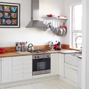 Photo of a small scandi l-shaped kitchen in London with a belfast sink, raised-panel cabinets, white cabinets, wood worktops, painted wood flooring and no island.