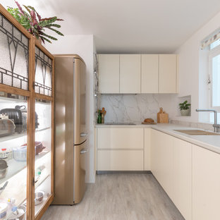 This is an example of a small contemporary galley enclosed kitchen in Sussex with no island, a submerged sink, flat-panel cabinets, white cabinets, white splashback, stone slab splashback, coloured appliances, beige floors and white worktops.