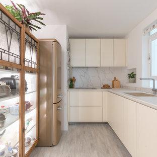 Свежая идея для дизайна: маленькая отдельная, параллельная кухня в современном стиле с врезной раковиной, плоскими фасадами, белыми фасадами, белым фартуком, фартуком из каменной плиты, цветной техникой, бежевым полом и белой столешницей без острова - отличное фото интерьера