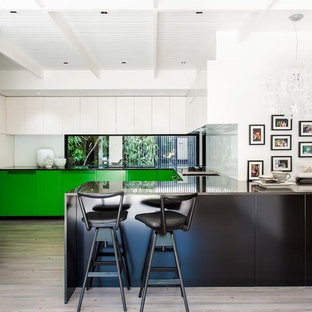 Design ideas for a contemporary u-shaped kitchen in Melbourne with flat-panel cabinets, green cabinets, window splashback, a peninsula, beige floor and black benchtop.