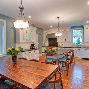 フィラデルフィアの広いトラディショナルスタイルのおしゃれなキッチン (アンダーカウンターシンク、白いキャビネット、ソープストーンカウンター、白いキッチンパネル、サブウェイタイルのキッチンパネル、シルバーの調理設備、無垢フローリング、茶色い床、黒いキッチンカウンター、格子天井) の写真
