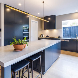 This is an example of a mid-sized contemporary kitchen in Melbourne with flat-panel cabinets, black cabinets, quartz benchtops, white splashback, porcelain splashback, black appliances, with island, beige floor, grey benchtop, a double-bowl sink and light hardwood floors.