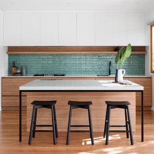 Photo of a contemporary single-wall kitchen in Melbourne with flat-panel cabinets, medium wood cabinets, blue splashback, medium hardwood floors, with island, brown floor and white benchtop.