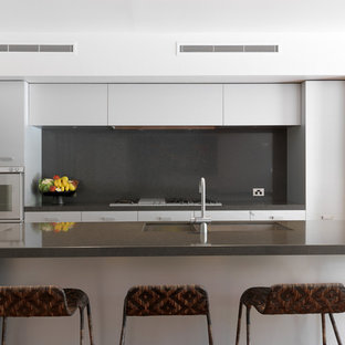 Inspiration for a contemporary galley kitchen in Melbourne with a double-bowl sink, flat-panel cabinets, white cabinets, black splashback and glass sheet splashback.