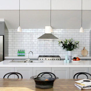 Inspiration for a transitional eat-in kitchen in Melbourne with shaker cabinets, grey cabinets, white splashback, subway tile splashback, stainless steel appliances, an island and a drop-in sink.