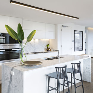 This is an example of a mid-sized contemporary galley kitchen in Melbourne with flat-panel cabinets, white cabinets, marble benchtops, stone slab splashback, stainless steel appliances, medium hardwood floors, with island, brown floor, white benchtop, a double-bowl sink and white splashback.