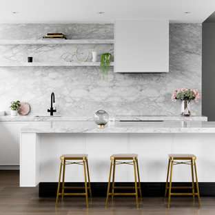 Photo of a contemporary galley kitchen in Melbourne with an undermount sink, flat-panel cabinets, white cabinets, marble benchtops, white splashback, marble splashback, black appliances, medium hardwood floors, with island, brown floor and white benchtop.