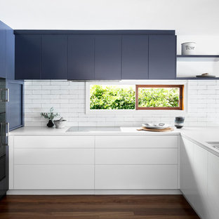 Mid-sized contemporary u-shaped eat-in kitchen in Melbourne with an undermount sink, flat-panel cabinets, blue cabinets, white splashback, black appliances, dark hardwood floors, quartz benchtops and window splashback.