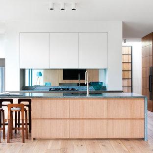 Ejemplo de cocina de galera, minimalista, con armarios con paneles lisos, puertas de armario de madera oscura, salpicadero con efecto espejo, suelo de madera en tonos medios, una isla y suelo marrón