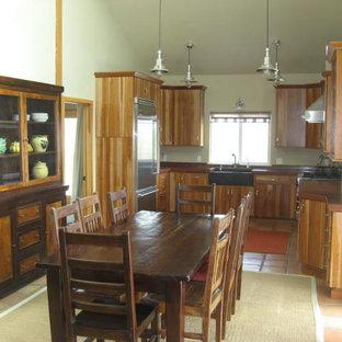 サンルイスオビスポの中くらいのカントリー風おしゃれなキッチン (エプロンフロントシンク、フラットパネル扉のキャビネット、中間色木目調キャビネット、銅製カウンター、シルバーの調理設備、テラコッタタイルの床、アイランドなし) の写真