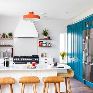 Große Klassische Küche in U-Form mit Unterbauwaschbecken, profilierten Schrankfronten, weißen Schränken, Küchengeräten aus Edelstahl, Halbinsel, braunem Boden und weißer Arbeitsplatte in Cork