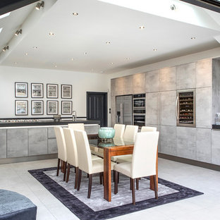 Inspiration for a large contemporary l-shaped kitchen/diner in London with flat-panel cabinets, distressed cabinets, stainless steel appliances, an island, grey floors, black worktops and granite worktops.