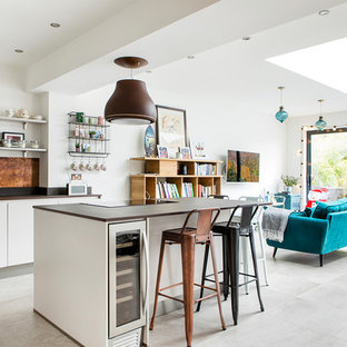 Photo of a medium sized contemporary l-shaped open plan kitchen in London with an island, flat-panel cabinets, metallic splashback, grey floors, brown worktops, a submerged sink, beige cabinets, quartz worktops and stainless steel appliances.