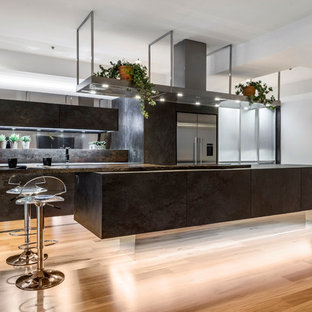 Photo of a mid-sized contemporary galley kitchen in Brisbane with flat-panel cabinets, wood benchtops, metallic splashback, mirror splashback, stainless steel appliances, light hardwood floors and with island.