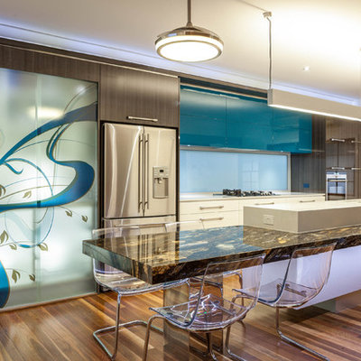 Mid-sized trendy galley medium tone wood floor eat-in kitchen photo in Brisbane with stainless steel appliances, flat-panel cabinets, marble countertops and an island