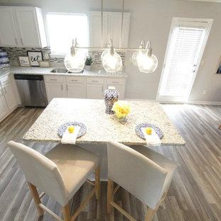 アトランタの広いトラディショナルスタイルのおしゃれなキッチン (ダブルシンク、フラットパネル扉のキャビネット、グレーのキャビネット、木材カウンター、グレーのキッチンパネル、磁器タイルのキッチンパネル、シルバーの調理設備、クッションフロア、茶色い床) の写真