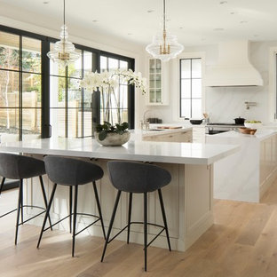 Transitional kitchen in Calgary with a double-bowl sink, recessed-panel cabinets, white cabinets, quartz benchtops, white splashback, panelled appliances, light hardwood floors, multiple islands and white benchtop.
