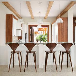 Inredning av ett exotiskt kök, med skåp i shakerstil, vita skåp, beige stänkskydd, stänkskydd i mosaik och en halv köksö