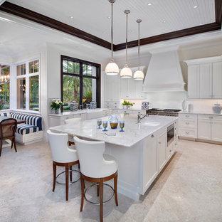 Große Tropische Wohnküche in L-Form mit Landhausspüle, Schrankfronten im Shaker-Stil, weißen Schränken, Marmor-Arbeitsplatte, Küchenrückwand in Weiß, Rückwand aus Stein, Elektrogeräten mit Frontblende, Kalkstein, Kücheninsel und beigem Boden in Miami