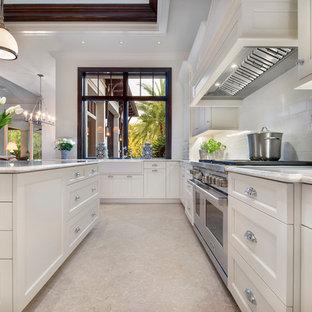 マイアミの大きいトロピカルスタイルのおしゃれなキッチン (エプロンフロントシンク、シェーカースタイル扉のキャビネット、白いキャビネット、大理石カウンター、白いキッチンパネル、石スラブのキッチンパネル、パネルと同色の調理設備、ライムストーンの床、ベージュの床) の写真