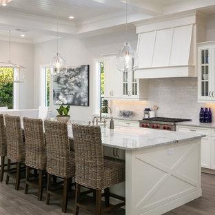 Mittelgroße, Offene Maritime Küche in L-Form mit Schrankfronten im Shaker-Stil, weißen Schränken, Küchengeräten aus Edelstahl, Kücheninsel, weißer Arbeitsplatte, Küchenrückwand in Weiß, Marmor-Arbeitsplatte, dunklem Holzboden, Landhausspüle, Rückwand aus Steinfliesen und braunem Boden in Orlando