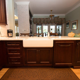 Mid-sized traditional kitchen designs - Inspiration for a mid-sized timeless u-shaped porcelain tile and brown floor kitchen remodel in Other with a farmhouse sink, recessed-panel cabinets, dark wood cabinets, quartz countertops, gray backsplash, mosaic tile backsplash, paneled appliances and white countertops
