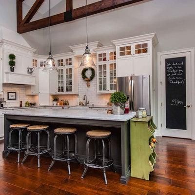 Inspiration for a timeless l-shaped kitchen remodel in Orlando with a farmhouse sink, glass-front cabinets, marble countertops, beige backsplash, subway tile backsplash, stainless steel appliances and white cabinets